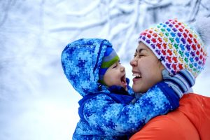 An Asian woman mother and her baby boy are playing in a snowy park in winter