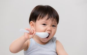 Toddler feeding self with spoon