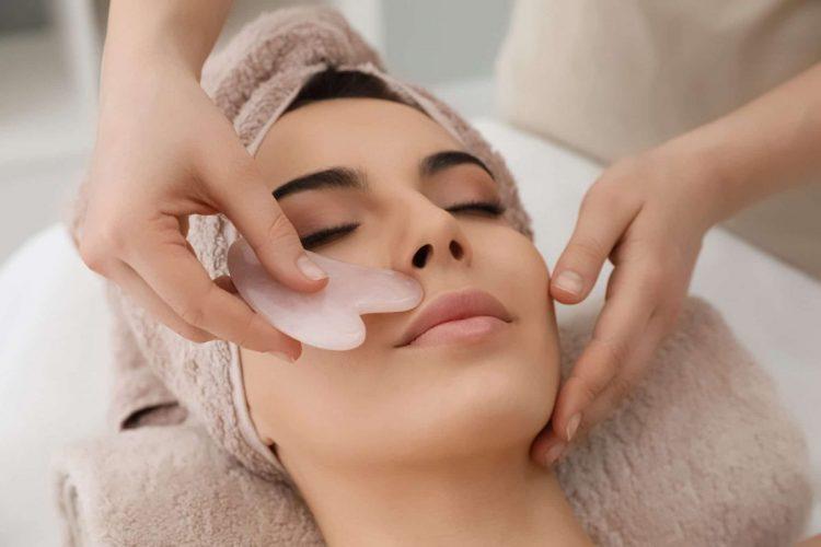 Rose quartz gua sha massage receiving facial massage with gua sha tool in beauty salon